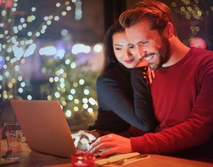 мъж и жена стоят пред лаптоп усмихнати
