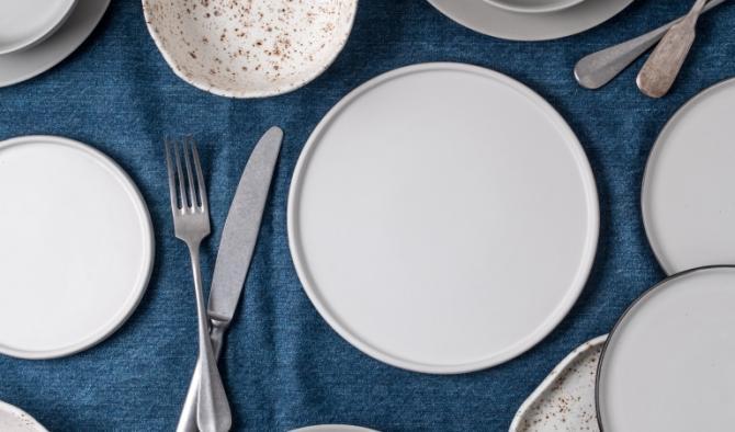 подредена маса с бели чинии и синя покривка